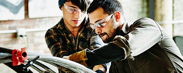 Metal workers adjusting support bars on project