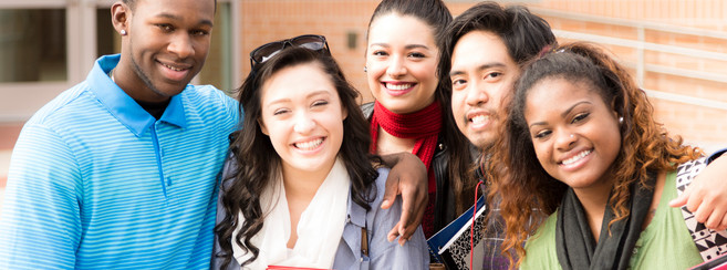 Happy, diverse group of college student friends hang out together before class begins.  They stand in front of a university school building holding books and looking at camera.  Hugs, smiles.
