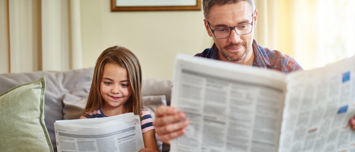 Shot of a father and daughter reading the newspaper