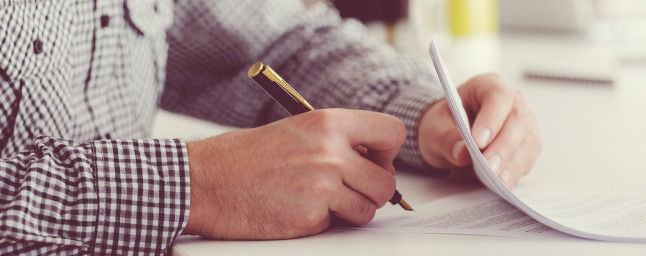 Man sitting at the table, holding a pen and signing contract. Focus on hands, unrecognizable person.