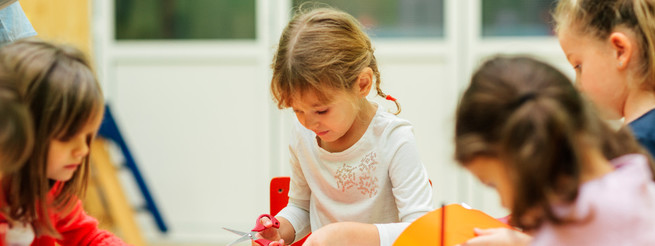 Group of children in kindergarten. Showing their imagination and skill and creativity. Selective focus of little girl sitting, holding scissors and cutting paper. Front view.