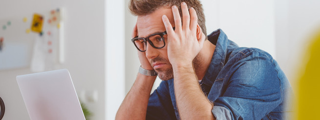 Worried man wearing jeans shirt and nerd glasses sitting at the table, holding head in hands, looking at laptop screen.
