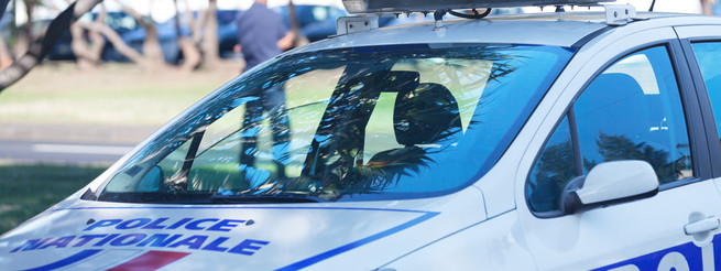 [b]Police Nationale[/b] car with a policemen in the background controlling the traffic.