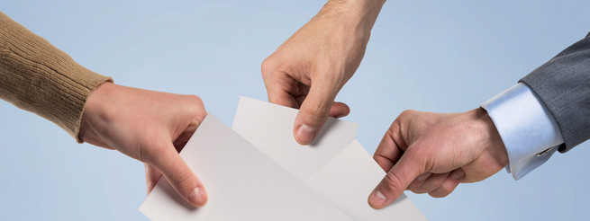 Hands inserting a blank vote